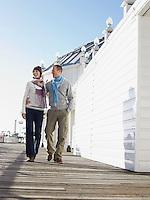 Embracing couple walking along pier