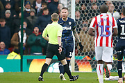 Leeds United defender Pontus Jansson (18) receives his first yellow card from Referee Gavin Ward during the EFL Sky Bet Championship match between Stoke City and Leeds United at the Bet365 Stadium, Stoke-on-Trent, England on 19 January 2019.