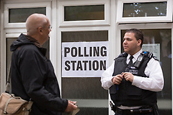 © Licensed to London News Pictures. 22/05/2014. London, UK. A member of the public speaks to a police officer standing outside a polling station at the Ogilvie Community Hall in Shadwell, East London on 22 May 2014.  All polling stations in Tower Hamlets today have a police presence to protect voters from any intimidation. Photo credit : Vickie Flores/LNP