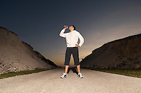 Mid adult man drinking water after jogging. evening