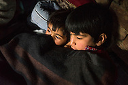 Azra, 5, and Igra, 8, gets ready for a nap in their temporary shelter in Narbal village, Jammu and Kashmir, India, on 24th March 2015. When the floods hit in the middle of the night, Shugufta and her family had to walk 5 miles to find shelter. Save the Children supported the family with shelter kits, blankets, hygiene items, food and tarpaulin, which they have used to build a temporary shelter next to their crumbled home. Photo by Suzanne Lee for Save the Children