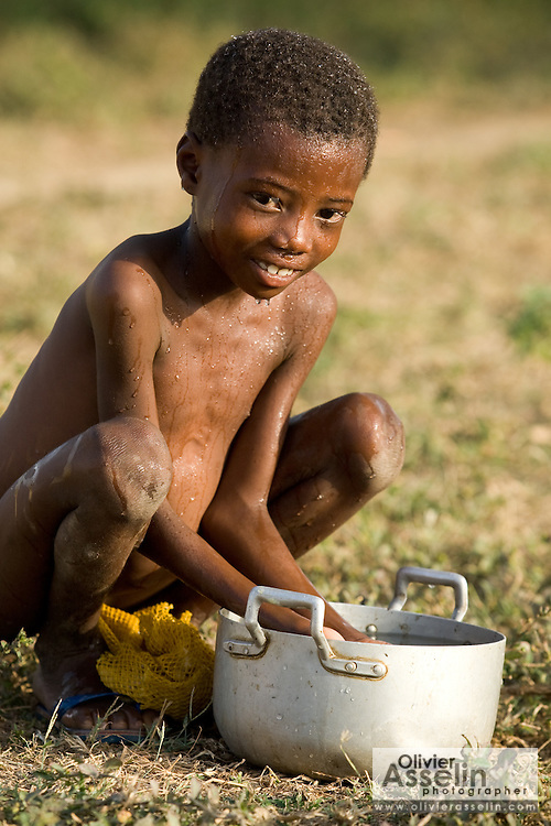 Child washing up with water from a metal pot.