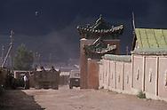 Mongolia. Ulaanbaatar. yurts area around Gandan monastery  OulanBator       / quartier de yourtes autour monastère de Gandan  OulanBator  Mongolie 2. Quartier de yourtes à OULAN BATOR. / La capitale s'élève dans une vallée du massif du KENTI. Un couple regagne leur domicile en banlieue, dans un des quartiers de yourtes délimités par de hautes palissades en bois. Au second plan se dresse le centre ville avec ses bâtiments administratifs et immeubles d'habitation en béton  / 37    L921009c    /  P0002773