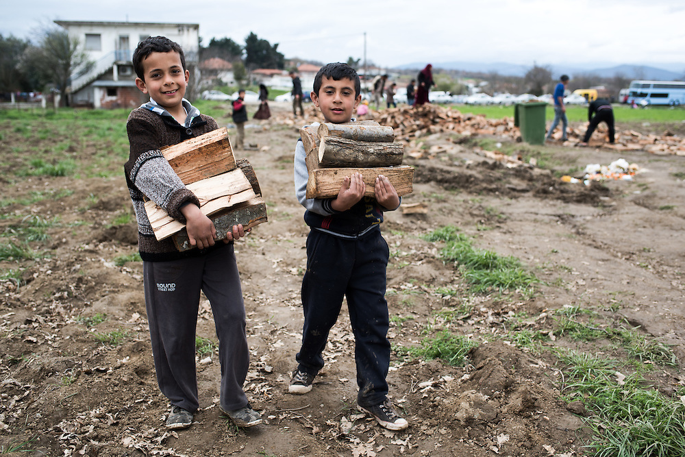 Two refugee kids are carrying logs to their tent.<br /> <br />  Thousands of refugees are stranded in Idomeni unable to cross the border. The facilities here are stretched to the limit and the conditions are appalling. It's raining, it's cold there is mud everywhere and there is no hope that the border will open anytime soon.