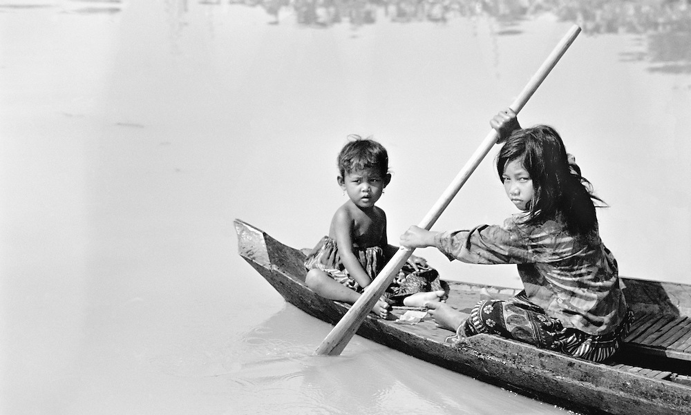 Two children on a dugout on the Tonle Sap river, Cambodia, 2003.