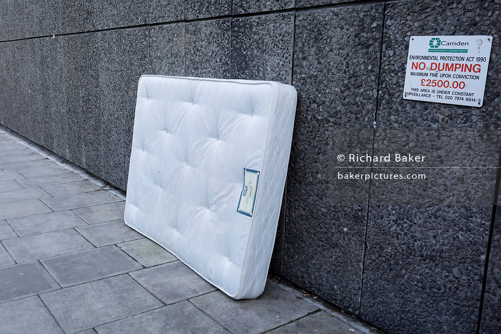A stained white mattress leaning against a wall next to a sign warning of £2,500 fines by the local authority for dumping or fly-tipping, on 6th February 2018, in the borough of Camden, London, England.