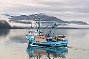 A commercial fishing boats heads out on the Passage Canal in Prince William Sound, Whittier, Alaska.