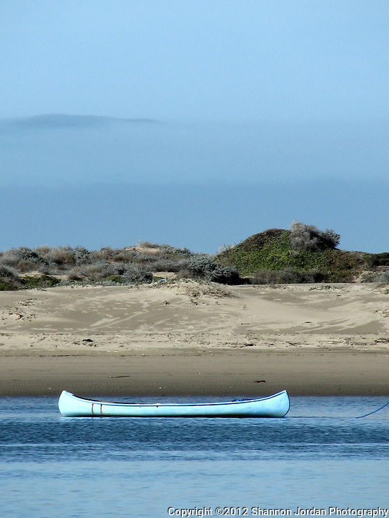 A blue canoe sits in the calm Morro Bay in front of the sand spit.