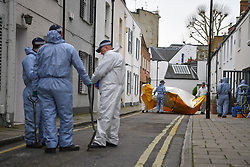 © Licensed to London News Pictures. 08/03/2019. Fulham, London, UK. Police officers dismantle the tent erected over the spot 17yr old Ayub Hassan collapsed and later died of stab wounds sustained in an attack yesterday afternoon. Four teenagers have been arrested in connection with the murder, the investigation continues. Photo credit: Guilhem Baker/LNP