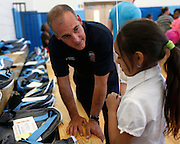 "Mark Pascuzzi, a Rochester Firefighter, helps Ivanis Gonzalez, 9, find her bag containing donated books at a celebration of the ""Help Me Read"" program at Enrico Fermi Elementary School No. 17 in Rochester on Monday, June 2, 2014. The tutoring program helped 137 children improve their reading ability, with some students making jumps of several grade levels in one year."
