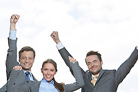 Portrait of excited businesspeople with arms raised on terrace against sky