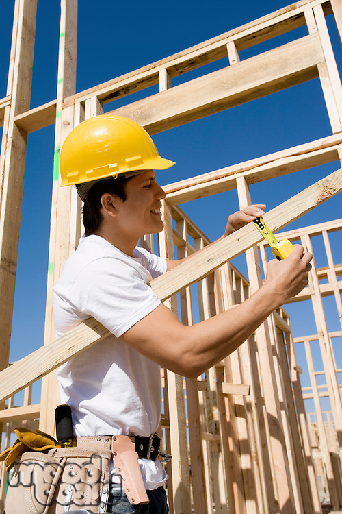 Construction worker measuring lumber at construction site