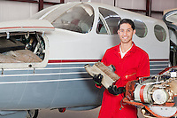 Portrait of male aviation mechanic with machine part standing in front of airplane