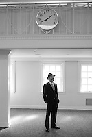 jewish groom with hat waits under a clock for his bride to arrive. looks like a train station that is all white. could be waiting to get into heaven.