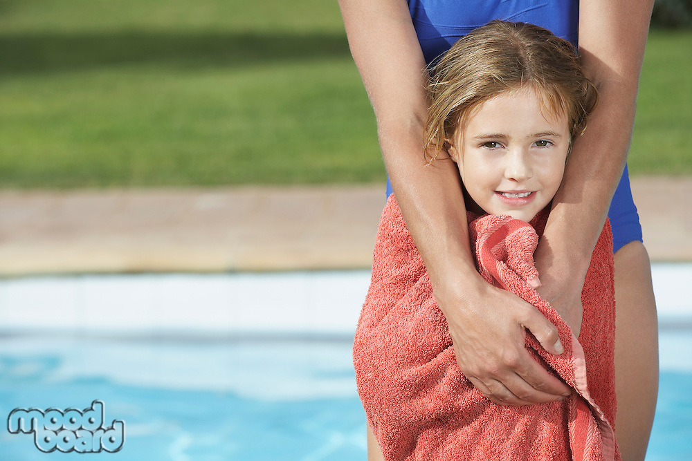 Portrait of girl (5-6) wrapped in towel mother behind her
