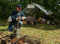 Greg Henderson puts on a pot of coffee during the 5th NH Volunteers Civil War encampment Saturday during Sanbornton Old Home Day.  (Karen Bobotas/for the Concord Monitor)