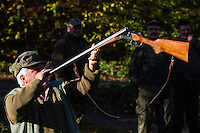 """Old Romanian hunter blowing on a rifle """"calling the lost dogs"""" after a driving hunt for Wild boar (Sus scrofa) in the forest area outside the village of Mehadia, Caras Severin, Romania."""