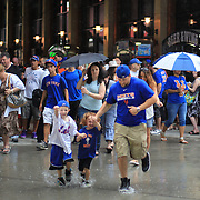 Two young New York Mets fans show their delight as they dodge the rain drops during a rain delay before the New York Mets V Arizona Diamondbacks Major League Baseball game  at Citi Field, Queens, New York. USA. 3rd July 2013. Photo Tim Clayton