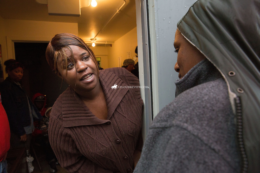Lisa Johnston | lisajohnston@archstl.org | Twitter: @aeternusphoto The St. Vincent de Paul food pantry at Blessed Teresa of Calcutta Parish operates once a month to help the poor supplement their needs. LaTasha Brown and Marquitta Watson waited in line as it rained.