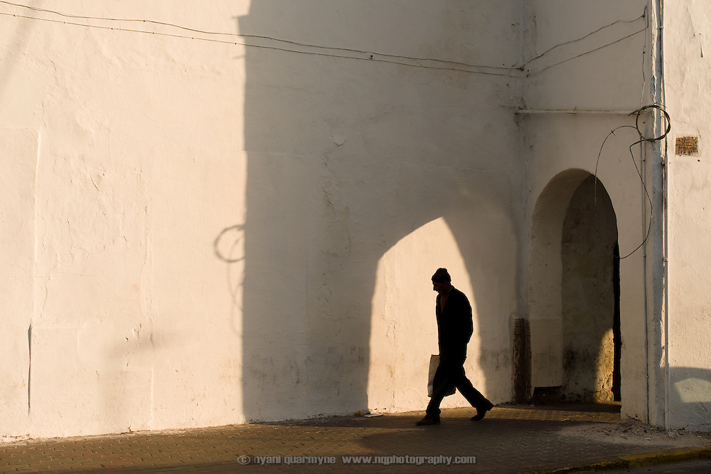A man is framed by the shadow of an archway as he walks along a street in Casablanca, Morocco on 7 September 2013.