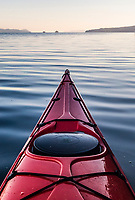 The bow of a sea kayak on glassy water in the Gulf Islands of British Columbia, Canada. Ganges Harbor, Salt Spring Island.