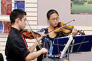Centerville High School Orchestra members Justin Lun (left) and Run Wei Wang perform holiday music at the WashingtonCenterville Public Library in Centerville, Monday, December 5, 2011.