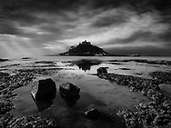 St. Michael's Mount is a rocky island 5 miles south of Penzance in Cornwall, England. Surmounted by an fortress-like abbey dedicated to St. Michael the Archangel.