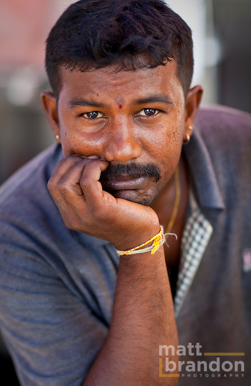 A Tamil man rests his head in his hand.