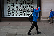 Shoppers walk past a window display that features numbers - part of a design theme called 'State of the Arts', at the Selfridges department store on Oxford Street, on 4th March 2019, in London England. Darren Almond's piece 'Chance Encounter 004', consists of a grid formed from rectangular panels, featuring fragmented numbers that appear to scroll across the surface. <br /> State of the Arts is a gallery of works by nine crtically-acclaimed artists in Selfridges windows to celebrate the power of public art. Each of the artists are involved in creating a site-specific artwork at one of the new Elizabeth line stations as part of the Crossrail Art Programme.