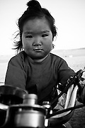 A young girl on a motorcycle in the Gobi Desert, Mongolia.