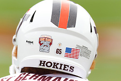 Nov 26, 2011; Charlottesville VA, USA;  Detailed view of the helmet of Virginia Tech Hokies long snapper Joe St. Germain (65) showing a sticker celebrating the 25th season of head coach Frank Beamer (not pictured) before the game against the Virginia Cavaliers at Scott Stadium.  Virginia Tech defeated Virginia 38-0. Mandatory Credit: Jason O. Watson-US PRESSWIRE