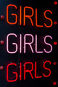 A detail of three Girls words repeated in neon, in the doorway of an adult shop in Soho, on 5th March 2019, in London, England.