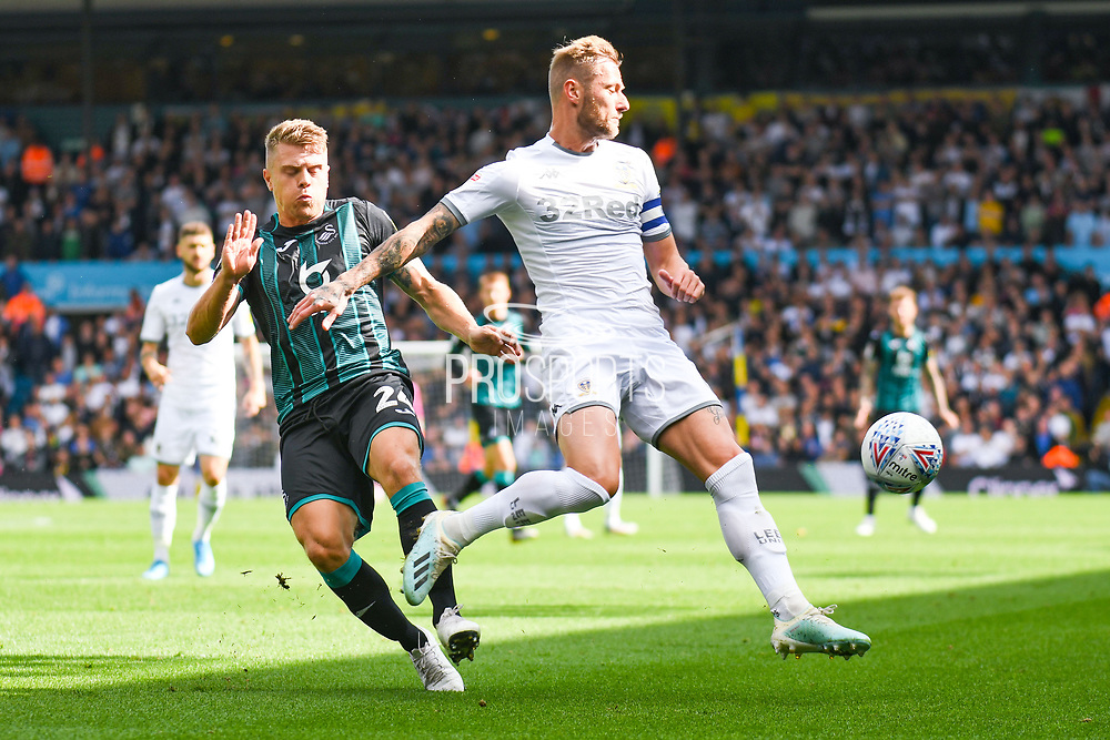Leeds United defender Liam Cooper (6) tackles Swansea City defender Jake Bidwell (24)  during the EFL Sky Bet Championship match between Leeds United and Swansea City at Elland Road, Leeds, England on 31 August 2019.