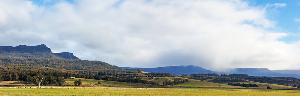 Panorama in the Meander Valley in northern Tasmania, with snow showers on the Great Western Tiers.  Mother Cummings Peak is visible on the left of the image.