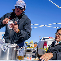 Edison Nelson, left, and Yolanda Ellis of the Navajo Nation Special Diabetes Project serve blue mush and other traditional foods to visitors during a harvest fest and farmers market outside Bashas Market in Window Rock Wednesday.
