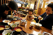 family with one child eating in a casual noodle restaurant Japan