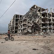 """Bet Hanon, quartiere a nord della striscia di Gaza quasi al confine con Erez. Una delle zone piu colpite dall'attacco israeliano """"Margine protettivo"""". Gli enormi palazzi sono completamente distrutti e sventrati. La popolazione, a distanza di sei mesi dalla fine della guerra, vive tra le macerie della propria casa, al freddo, senza luce, gas e acqua. Nella foto un ragazzino gira tra i palazzi cadenti con la sua bicicletta."""