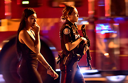 A police officer escorts a civilian away from the scene of a mass casualty incident in Toronto, ON, Canada on Sunday, July 22, 2018. A young woman has been killed and 13 others injured in a shooting incident in Toronto, Canadian police say. The Sunday night shooting happened in the Danforth and Logan avenues area. The gunman died in an exchange of fire. Among those injured is a young girl, described as in a critical condition. Police are appealing for witnesses. Photo by Frank Gunn/ABACAPRESS.COM