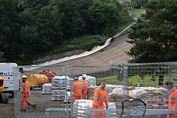 © Licensed to London News Pictures. 03/08/2019. Whaley Bridge, UK. Water is pumped away from inside the reservoir along a secure area of the slipway . The town of Whaley Bridge in Derbyshire remains evacuated after heavy rain caused damage to the Toddbrook Reservoir , threatening homes and businesses with flooding. Photo credit: Joel Goodman/LNP