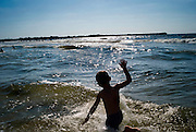 A Palestinian boy splashes into the water at the beach August 06, 2007 in Gaza City, Gaza. Palestinians families, citing the increased climate of security, have been flocking to beaches since Hamas took control of Gaza in June, something many say they had not been able to do for years...