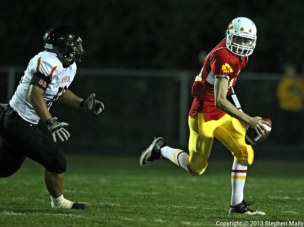 Marion's Trevor Hardman (16) scrambles away from Washington's Tama'aiga Leutele (58) during their game at Thomas Park Field in Marion on Friday, September 20, 2013.