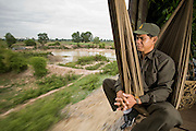 01 JULY 2006 - PHNOM PENH, CAMBODIA: A train security officer watches the Cambodian countryside roll by on the Phnom Penh - Battambang train. While much of Cambodia's infrastructure has been rebuilt since the wars which tore the country apart in the late 1980s, the train system is still in disrepair. There is now only one passenger train in the country. It runs from Phnom Penh to the provincial capitol Battambang and it runs only one day a week. It takes 12 hours to complete the 190 mile journey.  Photo by Jack Kurtz / ZUMA Press