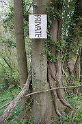 Private sign hanging at 90 degrees on trees in Kent woodland.