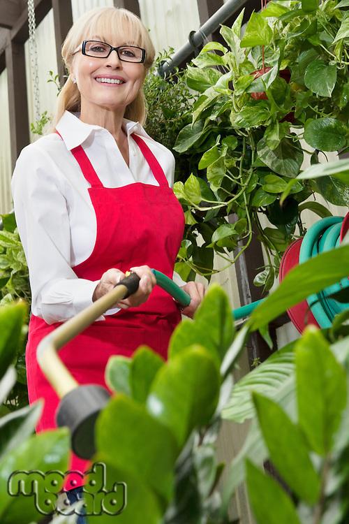 Portrait of a senior female gardener spraying pesticide on plants in botanical garden