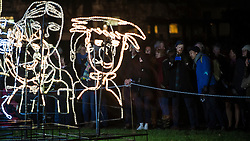 "© Licensed to London News Pictures. 15/01/2016. London, UK.  Visitors line up to see ""Brothers and Sisters"" by Ron Haselden on display in Grosvenor Square.  The work forms part of Lumiere London, a major new light festival which is into the second of four evenings and featuring artists who work with light.  The event is produced by Artichoke and supported by the Mayor of London.  Photo credit : Stephen Chung/LNP"