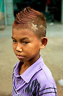 A young boy proud of his NLD symbol with the star and the fighting peacock, shaved on his hair..Mandalay, Myanmar. 2012