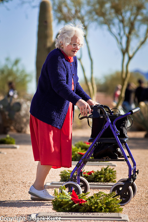 09 DECEMBER 2011 - PHOENIX, AZ:  A woman walks through the National Cemetery in Phoenix Saturday. Several hundred volunteers and veterans gathered at the National Memorial Cemetery of Arizona in Phoenix Saturday to lay Christmas wreaths on headstones, a tradition started by Wreaths Across America. Wreaths Across America is a nonprofit organization founded to continue and expand the annual wreath laying ceremony at Arlington National Cemetery begun by Maine businessman, Morrill Worcester, in 1992.   PHOTO BY JACK KURTZ
