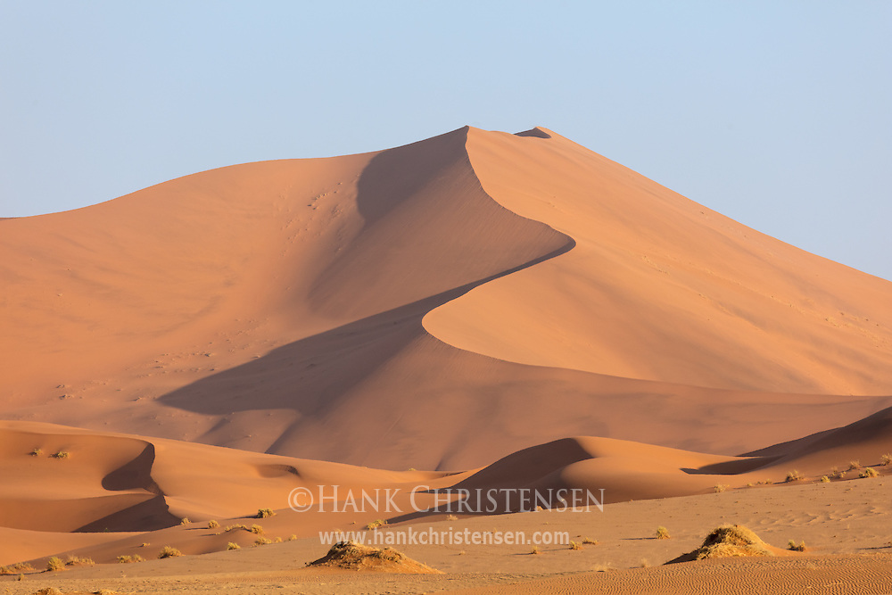 A massive sand dune glows red orange in the setting sun, Namib-Naukluft National Park, Namibia.