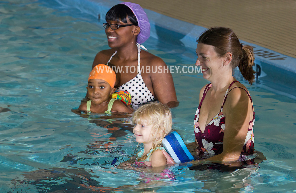 Middletown, New York - Mothers help their children learn to swim during a parent and child swimming class at the YMCA of Middletown on Nov. 5, 2014.