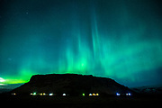 Aurora Borealis spectacular view of the Northern Lights in the sky over Mount Petursey Mountain at Vellir near Vik in South Iceland